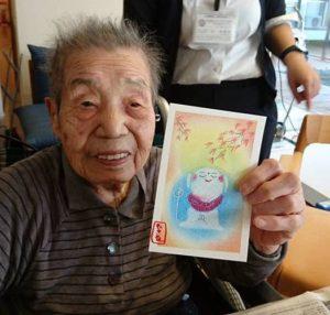 パステルアートを高齢者介護施設で実施した様子です。認知症の男性がパステルアートで描いたお地蔵様の絵を嬉しいそうに見せて記念撮影しています。
