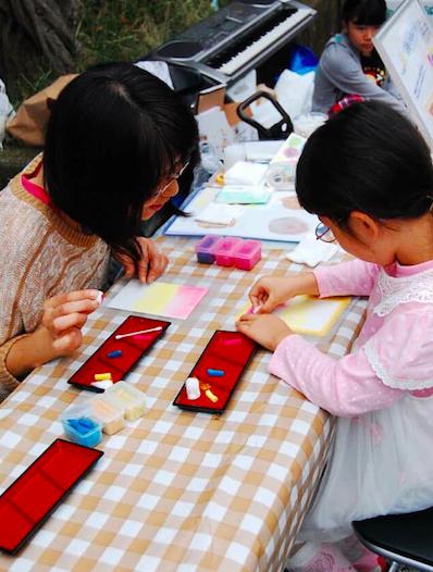 パステルアートインストラクター田崎さんが、発達障害の子どもにパステルアートを教えている様子です。